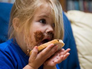дете яде филия с шоколад, мръсно дете, момиченце