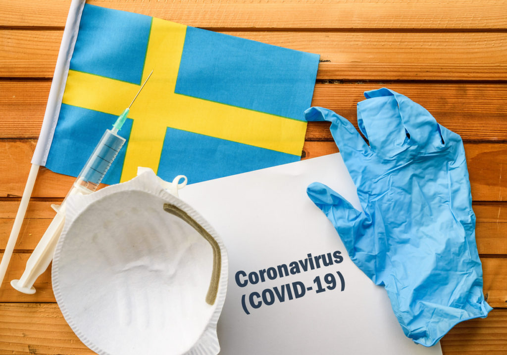 Flag of Sweden,, vaccine, face mask for virus, glove and paper sheet with words Coronavirus COVID-19