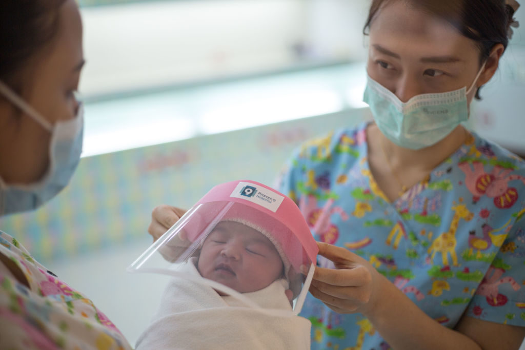 BANGKOK, THAILAND - APRIL 13: A nurse seen holding a new born baby wearing a tiny face shield against the coronavirus (COVID-19) pandemic at Praram 9 Hospital on April 13, 2020 in Bangkok, Thailand. Thailand's Health Ministry recorded a total of 2,579 infections, 40 death and 1,288 recovered since the beginning of the outbreak. (Photo by Guillaume Payen/Anadolu Agency via Getty Images)