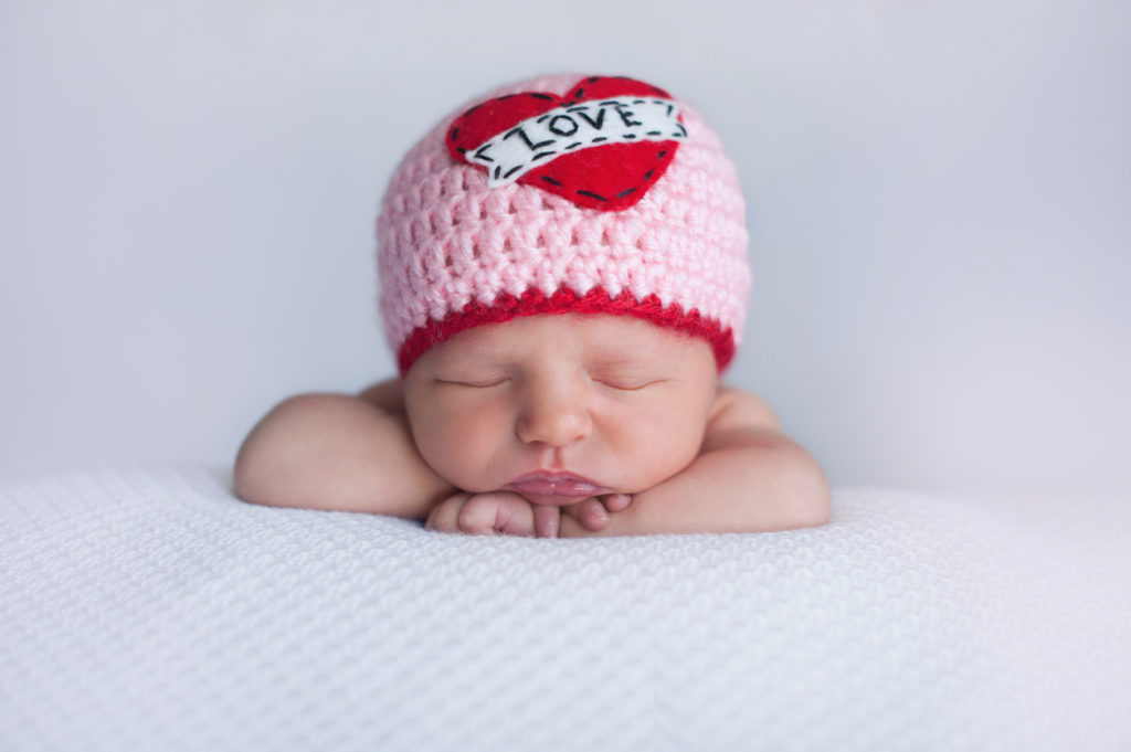 "Portrait of a seven day old sleeping baby girl wearing a crocheted ""Love"" beanie. Cute shot to use for Valentine's Day."