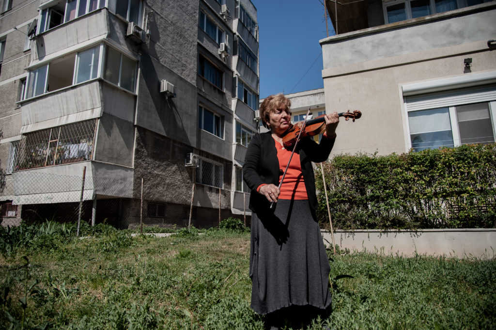 An elderly women plays the violin in front of the apartment building she lives in to lift the spirits of her neighbors during quarantine. Greta Burova, 80, is a performer and a violin teacher in the National School of Arts Dobri Hristov in Varna, Bulgaria. She says that music is the language she speaks best so she plays for her neighbors every day to bring joy in their lives, Varna, Bulgaria on April 27, 2020 (Photo by Hristo Rusev/NurPhoto via Getty Images) An elderly women plays the violin in front of the apartment building she lives in to lift the spirits of her neighbors during quarantine. Greta Burova, 80, is a performer and a violin teacher in the National School of Arts Dobri Hristov in Varna, Bulgaria. She says that music is the language she speaks best so she plays for her neighbors every day to bring joy in their lives, Varna, Bulgaria on April 27, 2020 (Photo by Hristo Rusev/NurPhoto via Getty Images)