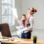Multitasking businesswoman holding a pile of paper documents with her baby son standing at the office