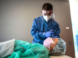 "SANT CUGAT, SPAIN - MAY 11: Dr. Ivan Manero injects a botox treatment to Cristina wearing PPE kit as a part of the new protocols for action and protection against the Covid 19 pandemic during the demonstration for the photographer at IM Ivan Manero Aesthetic Surgery Clinic  on May 11, 2020 in Sant Cugat, Spain. Some parts of Spain have entered the so-called ""Phase One"" transition from its coronavirus lockdown, allowing many shops to reopen as well as restaurants who serve customers outdoors. Locations that were harder hit by coronavirus (Covid-19), such as Madrid and Barcelona, remain in a stricter ""Phase 0"" quarantine. (Photo by Miquel Benitez/Getty Images)"