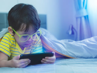 Cute little child watch movie on smartphone at bed. Dangers of blue light can damage eyes. Handsome little boy can be age related macular degeneration from blue light, wear eyeglasses since childhood