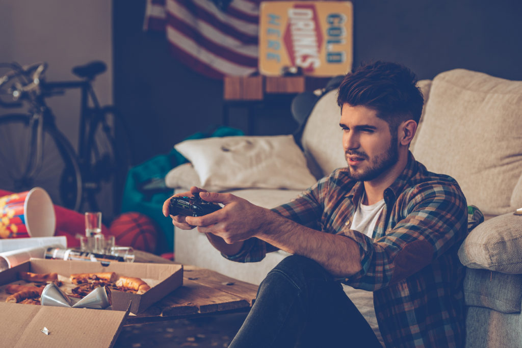 Frustrated young man holding joystick while sitting on the floor in messy room after party