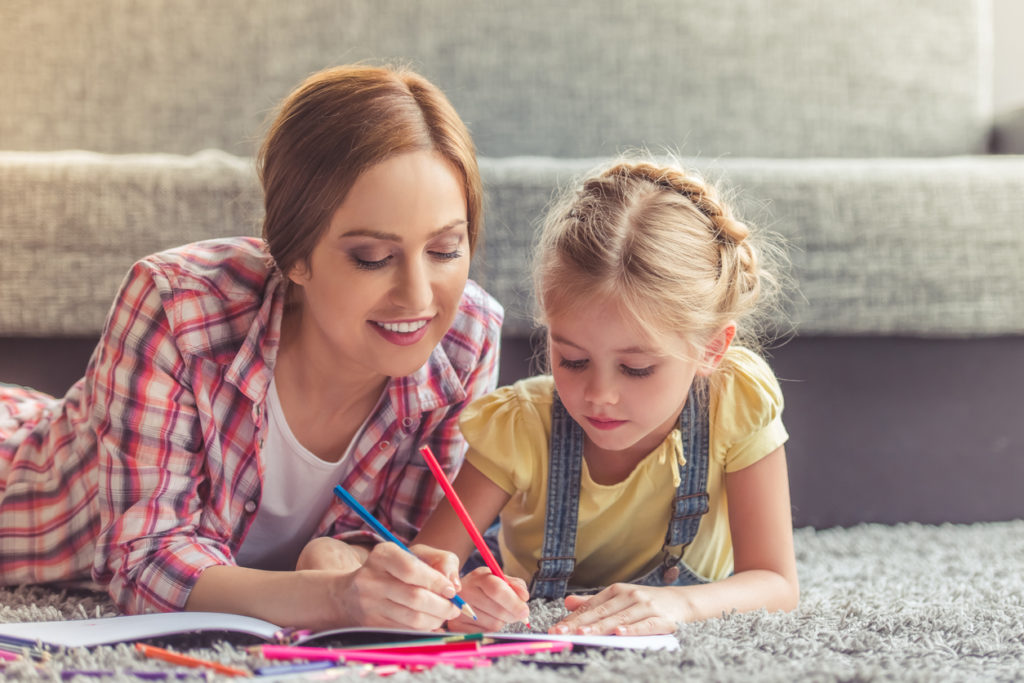 Cute little girl and her beautiful mother are drawing and smiling while lying on the floor at home