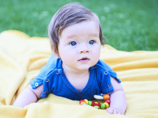 Newborn girl with blue eyes in the beautiful park outdoors, lies on a blanket wearing blue babybody and looking into camera