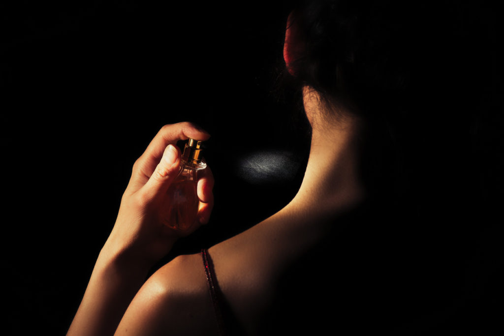 Woman sprays perfume on her neck with a black background.
