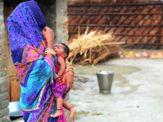 An indian woman stands with her child,  outside of her home  in Harvansh pur village, vaishali District , some 35 kms from MuzaffarPur , Bihar on June 22, 2019 .Three more children with symptoms of Acute Encephalitis Syndrome (AES) died at a hospital in Bihar's Muzaffarpur district on June 21 taking the toll to 128 . The high number of deaths this year has been blamed on hypoglycemia or sudden drop in blood sugar levels, which some experts attribute to malnutrition and consumption of unripe litchi -- a fruit grown in abundance in north Bihar -- on an empty stomach and failure to administer glucose within four hours of the onset of fever and other symptoms. (Photo by Ritesh Shukla/NurPhoto via Getty Images)