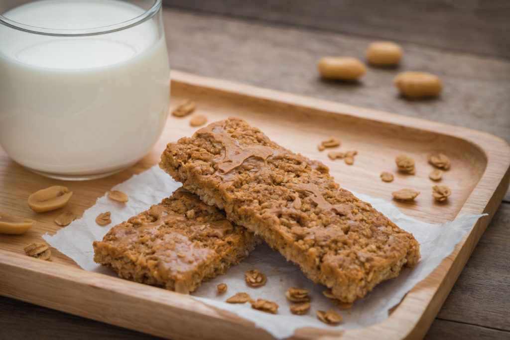 Granola bars on wooden plate and glass of milk