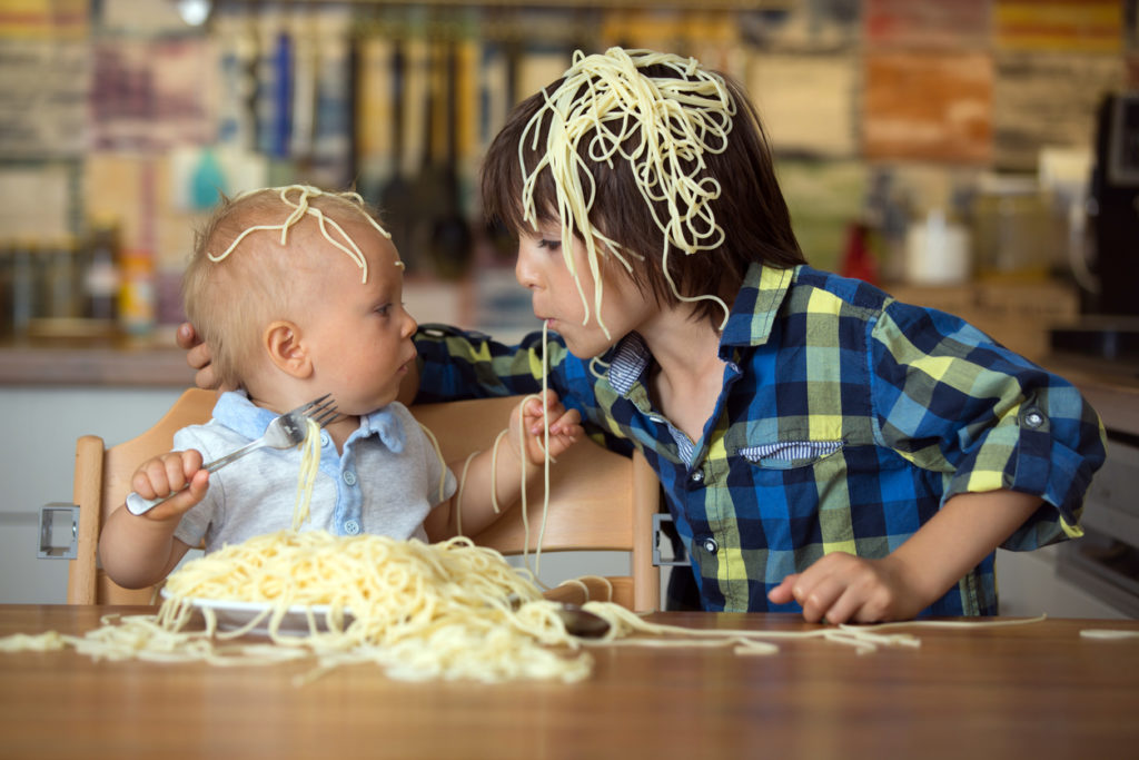 Little baby boy and his older brother, toddler child, eating spaghetti for lunch and making a mess at home in kitchen