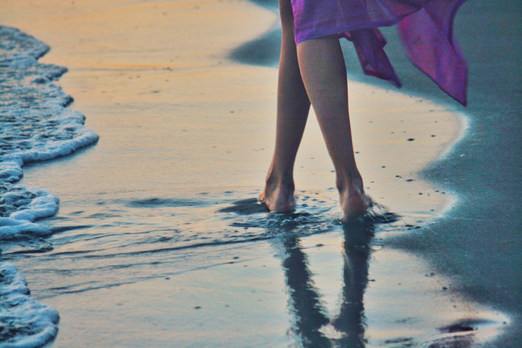 Woman feet walking barefoot on sandy beach by sea waves Ada Bojana Montenegro