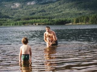 July 8, 2012 - Norway: father is holding one son in the water of a lake in summer after just throwing him in the air while a brother is coming for his turn, togetherness, bonding, childhood memories and happiness.
