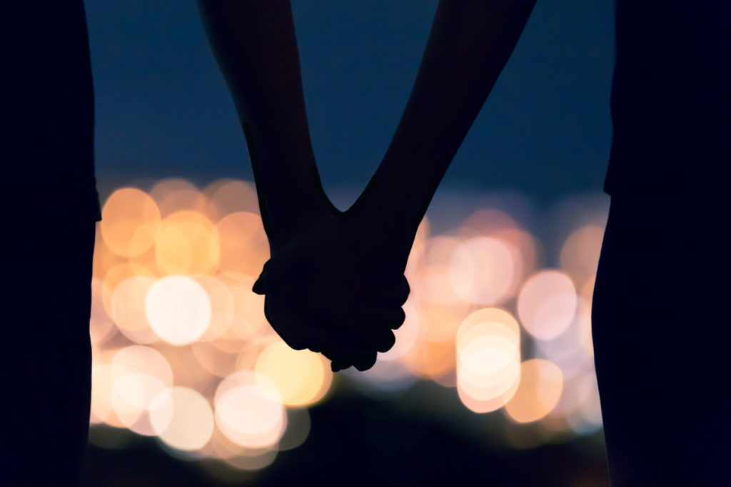 Couple holding hands against city night lights.