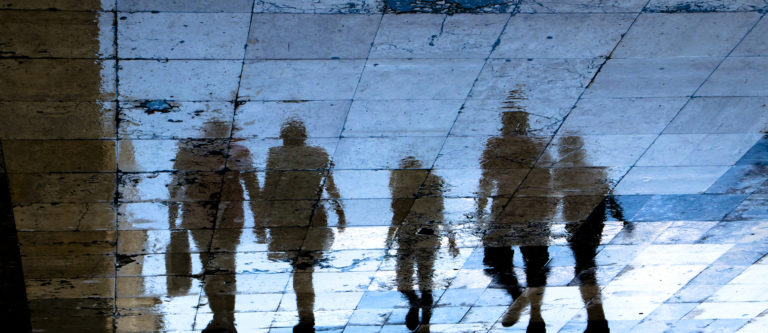 Blurry reflection shadow silhouette on wet city sidewalk of mysterious people walking away the night, low angle view