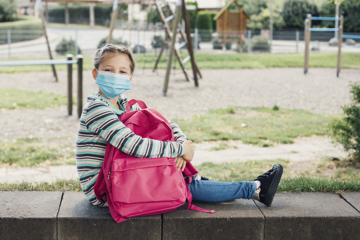 A girl in a protective mask sits in the schoolyard with her pink backpack. Rest from study. Keeping distance