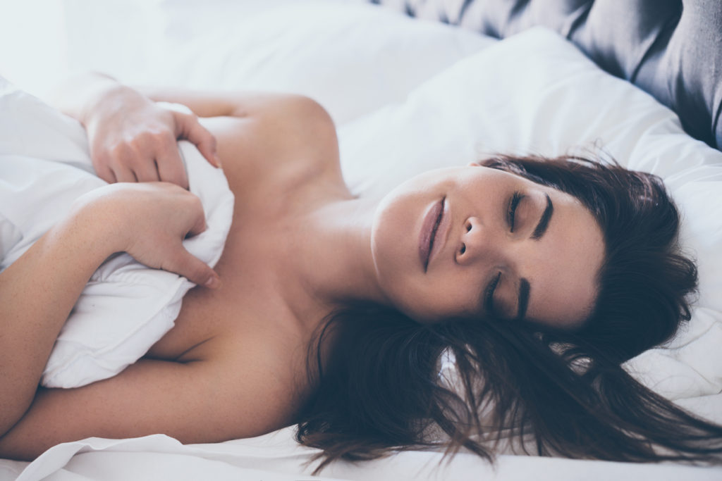 Close-up of beautiful young woman lying in bed cowered with blanket and sleeping