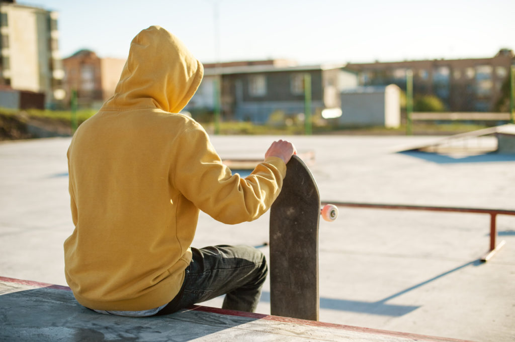 Close-up of a young hipster dressed in a sweatshirt and jeans sitting sad in a skate park and holding a skateboard