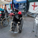 "SOFIA, BULGARIA - SEPTEMBER 10: Wheelchairs are chained to one another in front of the camp of the parallel protest of parents of children with disabilities on September 10, 2020 in Sofia, Bulgaria. The protesting parents of children with disabilities has been going on for more than a year now. Their slogan is ""The system is killing them"". On one wheelchair are seen stickers with the faces of Bulgarian politicians from the current government.  For weeks now thousands of people have been taking part in daily protests against corruption, demanding the resignation of the government of Boyko Borissov, in power since 2009. (Photo by Hristo Rusev/Getty Images)"