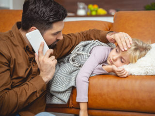 Worried man talking with doctor on cellphone while sick little girl lying on couch stock photo