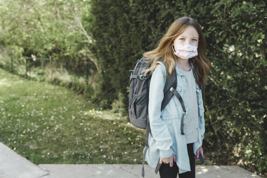 pretty girl with nose mouth mask goes to school after the corona quarantine