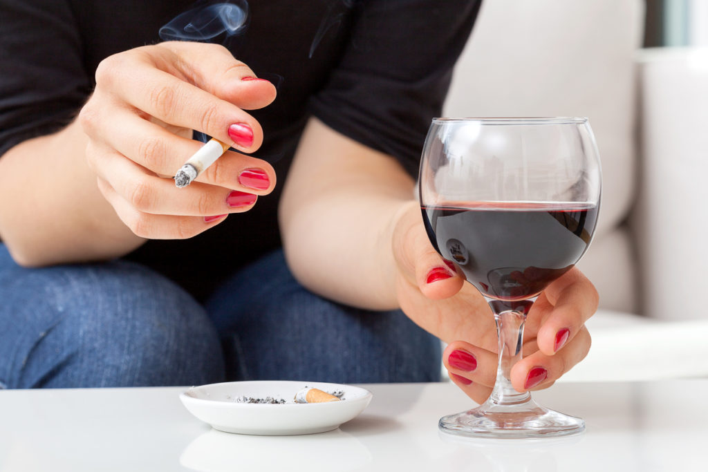Young woman addicted to cigarettes and alcohol sitting by the table at home