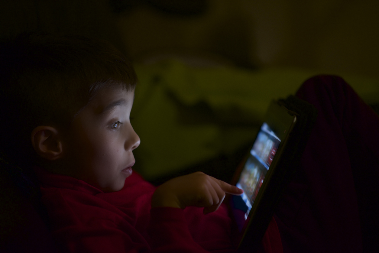puzzled child use tablet in the night without permission