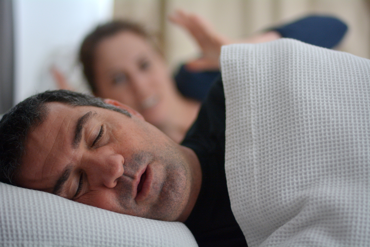 Woman (age 30) suffers from her male partner (age 40) snoring in bed. Noise concept. Real people. Copy space