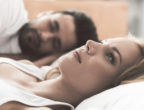 Nervous young woman is lying on bed and thinking seriously. Her husband is sleeping on background