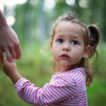 Little cute girl holding mother's hand< single parent, copy space