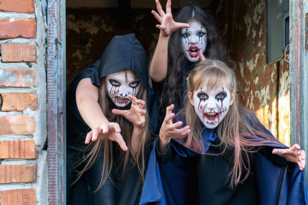 Three little teenage girls in zombie costumes go out the door of an old ruined building and look frighteningly at the camera. Halloween and day of the dead concept.