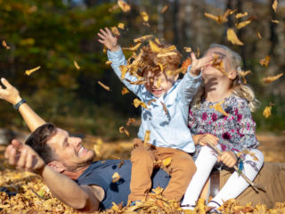 Happy father and children playing with autumn leaves in forest