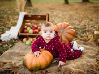 Little girl leans on a pumpkin.