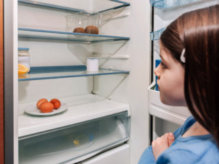 Worried girl looking at the almost empty fridge due to a crisis