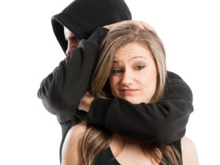 Mad male aggressor and confident and fearless female laughing not impressed. Harassment concept on white background.