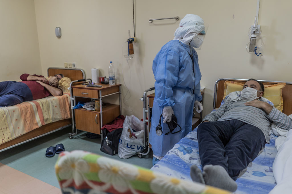 HASKOVO, BULGARIA - NOVEMBER 05: Doctor Mariyana Chatalova is seen wearing protective equipment and taking care of a coronavirus patient in the ICU of Haskovo Hospital on November 05, 2020 in Haskovo, Bulgaria. For the last 24 hours 4,054 new cases of COVID-19 have been registered in Bulgaria. In Haskovo district alone, the number of new positive cases is 61. All patients with severe cases of COVID-19 are treated at the district hospital in Haskovo. There are currently 80 patients there, 20 more than the hospital's capacity. The intensive care unit needs to be turned into a COVID ward, which means that people with other emergency problems will not be able to receive help in this hospital. Record numbers of daily infections has seen COVID-19 lockdowns and curbs put in place across Europe but has met with widespread resistance with hospitals buckling under the strain of new admissions. (Photo by Hristo Rusev/Getty Images)