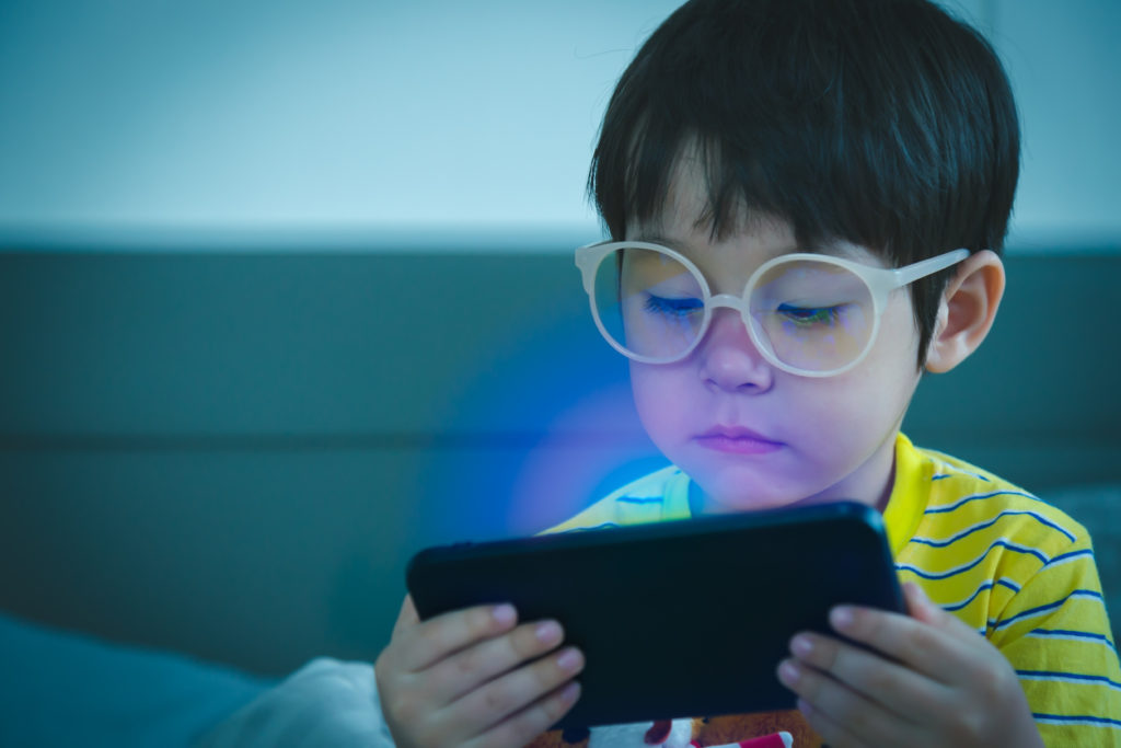 Cute little child watching cartoon on smartphone in the dark room. Dangers of blue light damage his eyes. Handsome little boy can get age related macular degeneration of blue light, he wear eyeglasses