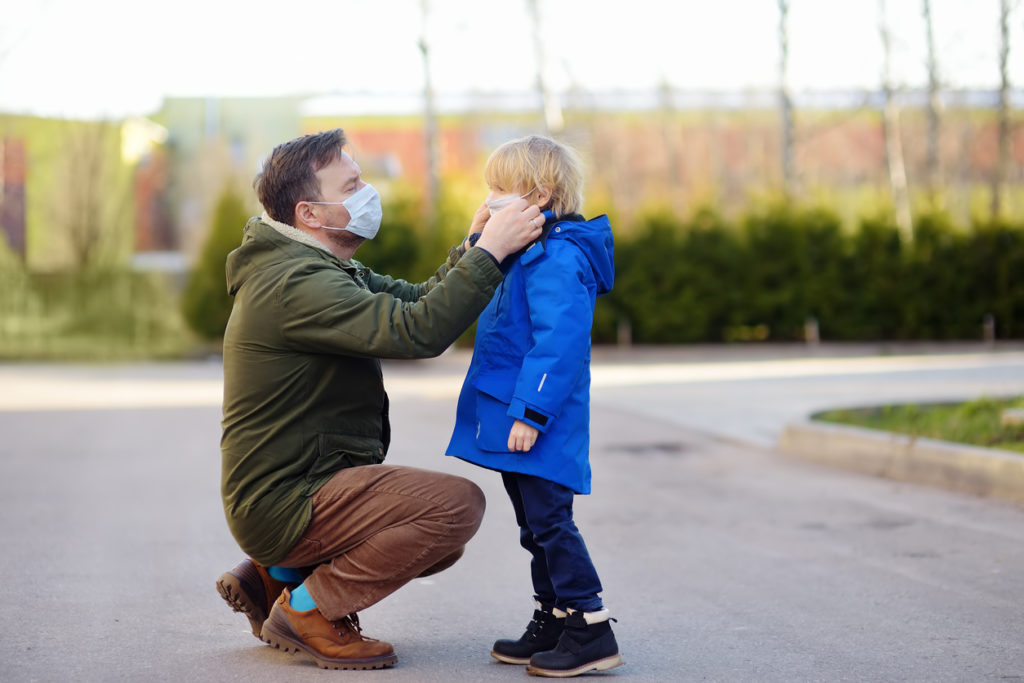Mature man wearing a protective mask puts a face mask on a his son in airport, supermarket or other public place. Safety during COVID-19 outbreak. Epidemic of virus covid. Coronavirus pandemic.