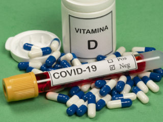 Vitamin D container with capsules around it and a vacuum tube with the text Covid-19