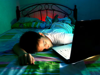Photo of a Young Teen sleeping in front of a laptop computer and on a bed
