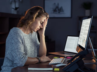 Mature and tired businesswoman working in the office until night. Portrait of a casual stressed lady with headache at desk near desktop computer. Exhausted business woman working late night at computer in office.