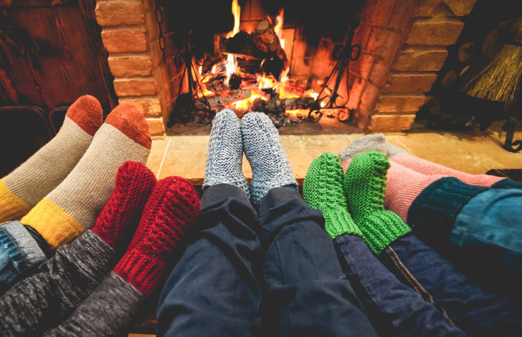 Legs view of happy family wearing warm socks in front of fireplace - Winter, love and cozy concept - Focus on center grey woolen socks