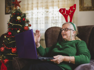 Grandmother talking to her grandchildren on the computer for Christmas.