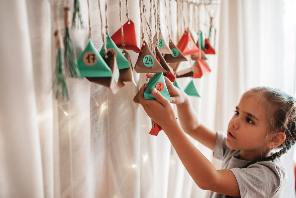 Cute little kid opening handmade advent calendar with color paper triangles. Sweets and candies are hidden in colorful triangles hanging on branch. Seasonal activity for kids, family winter holidays