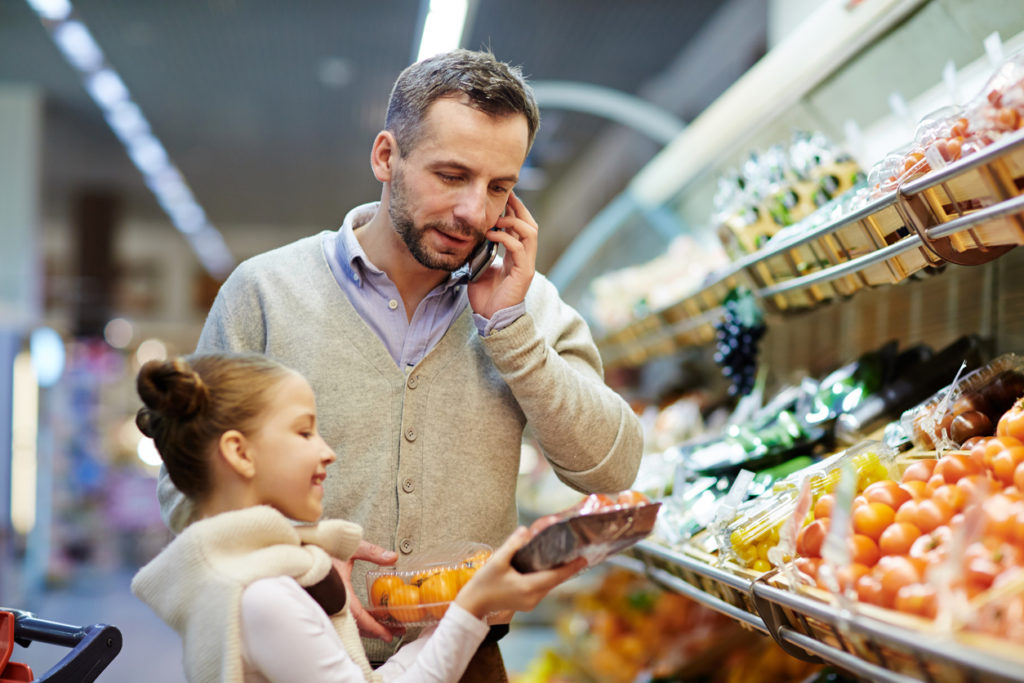 Portrait of man grocery shopping with daughter: speaking by phone calling wife to ask what vegetables to buy