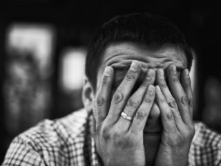 Sad and depressed young man covering face - Feeling depressed background concept - Marriage Failure Concept - Depressed Young Adult Portrait - Lonely Sad Widower - Black and White Monochrome