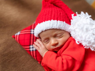 Cute newborn baby in Santa hat. Sleeping baby on a dark background. Closeup portrait of newborn baby. Baby goods packing template. Nursery. Medical and healthy concept. Christmas. New Year