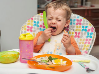 A 2-year-old baby girl grimaces and cries as she eats a meal on a high chair.  [MR: Maude Saez O'Donoghue]. (Photo by: Pascal Saez/VW Pics/Universal Images Group via Getty Images)