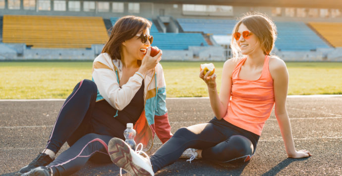 Healthy lifestyle and healthy food concept. Smiling fitness mother and teen daughter together eating apple sitting on stadium after training on sunny spring day.