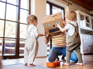Two happy toddler children with a father and carboard monster playing indoors at home.